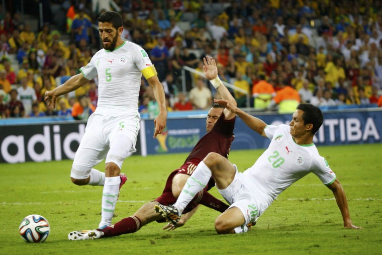 Russia's Alexander Kerzhakov (Center) fights for the ball with Algeria's Rafik Halliche (Left) and Aissa Mandi during their 2014 World Cup Group H soccer match at the Baixada arena in Curitiba June 26, 2014. (Murad Sezer/Reuters photo)