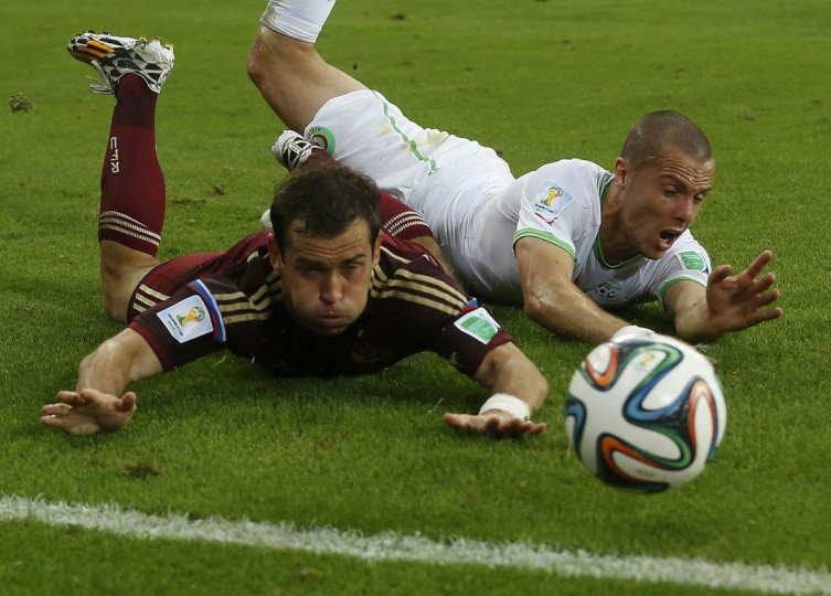Algeria's Djamel Mesbah (Right) fouls Russia's Alexander Kerzhakov during their 2014 World Cup Group H soccer match at the Baixada arena in Curitiba June 26, 2014. Mesbah received a yellow card for the foul. (Maxim Shemetov/Reuters photo)