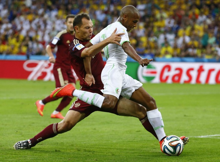 Russia's Sergey Ignashevich (Left) fights for the ball with Algeria's Yacine Brahimi during their 2014 World Cup Group H soccer match at the Baixada arena in Curitiba June 26, 2014. (Damir Sagolj/Reuters photo)