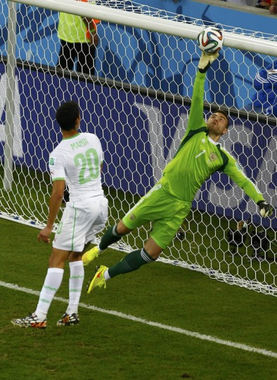 Russia's goalkeeper Igor Akinfeev (Right) saves the ball in front of Algeria's Aissa Mandi during their 2014 World Cup Group H soccer match at the Baixada arena in Curitiba June 26, 2014. (Amr Abdallah Dalsh/Reuters photo)