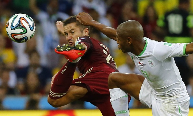 Russia's Alexey Kozlov (Left) kicks the ball next to Algeria's Yacine Brahimi during their 2014 World Cup Group H soccer match at the Baixada arena in Curitiba June 26, 2014. (Damir Sagolj/Reuters photo)