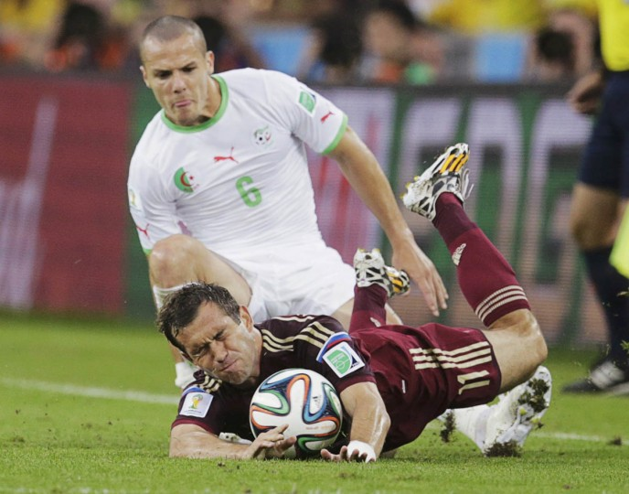 Russia's Alexander Kerzhakov falls after being fouled by Algeria's Essaid Belkalem (back) during their 2014 World Cup Group H soccer match at the Baixada arena in Curitiba June 26, 2014. (Henry Romero/Reuters photo)