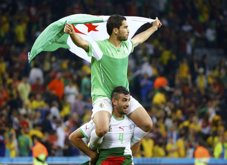Algeria's Essaid Belkalem carries teammate Abdelmoumene Djabou on his shoulders as they celebrate the end of their 2014 World Cup Group H soccer match against Russia at the Baixada arena in Curitiba June 26, 2014. Algeria made it into the last 16 of the World Cup for the first time with a 1-1 draw against Russia. (Murad Sezer/Reuters photo)