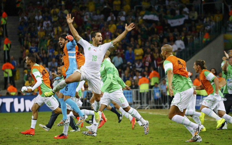 Algeria's Abdelmoumene Djabou (Center) celebrates with his teammates at the end of their 2014 World Cup Group H soccer match against Russia at the Baixada arena in Curitiba June 26, 2014. (Murad Sezer/Reuters photo)