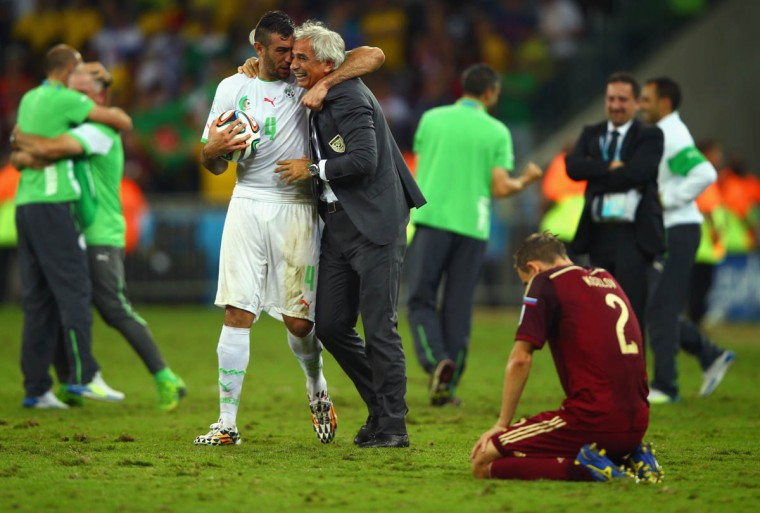 Essaid Belkalem of Algeria celebrates with head coach Vahid Halilhodzic as a dejected Aleksei Kozlov of Russia looks on during the 2014 FIFA World Cup Brazil Group H match between Algeria and Russia at Arena da Baixada on June 26, 2014 in Curitiba, Brazil. (Clive Rose/Getty Images)