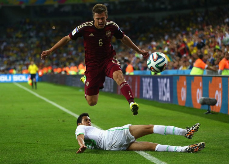 Aissa Mandi of Algeria tackles Maksim Kanunnikov of Russia during the 2014 FIFA World Cup Brazil Group H match between Algeria and Russia at Arena da Baixada on June 26, 2014 in Curitiba, Brazil. (Jamie Squire/Getty Images)