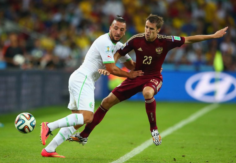 Nabil Ghilas of Algeria and Dmitry Kombarov of Russia compete for the ball during the 2014 FIFA World Cup Brazil Group H match between Algeria and Russia at Arena da Baixada on June 26, 2014 in Curitiba, Brazil. (Julian Finney/Getty Images)