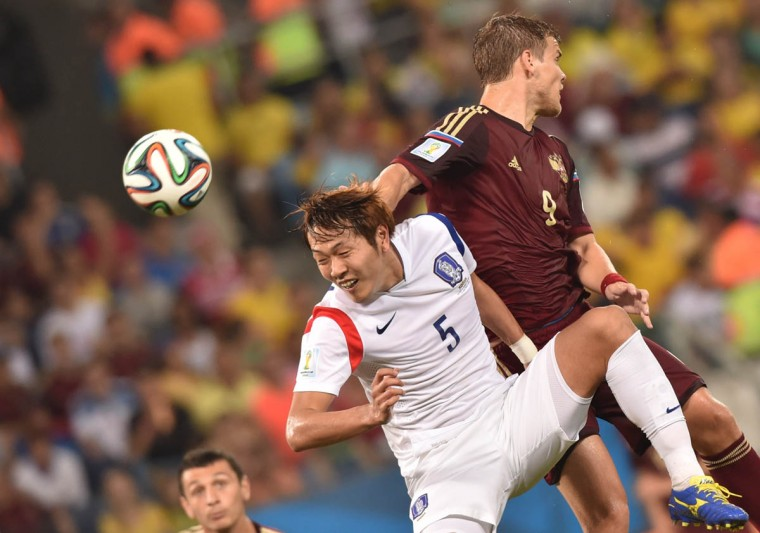 South Korea's defender Kim Young-Gwon (Left) and Russia's forward Alexander Kokorin vie during the Group H football match between Russia and South Korea in the Pantanal Arena in Cuiaba during the 2014 FIFA World Cup on June 17, 2014. (Kirill Kudryavtsev/Getty Images)