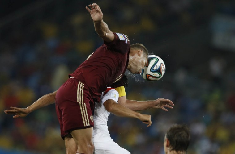 Russia's defender Vasily Berezutsky (Left) heads the ball during the Group H football match between Russia and South Korea in the Pantanal Arena in Cuiaba during the 2014 FIFA World Cup on June 17, 2014. (Adrian Dennis/Getty Images)