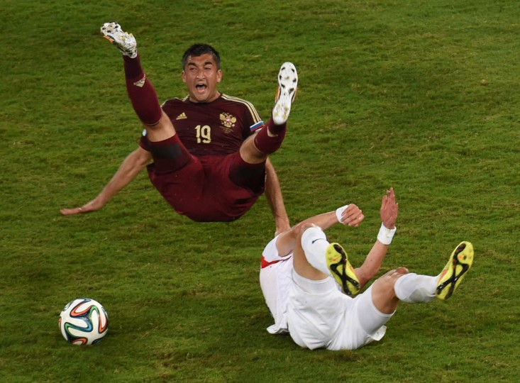 Russia's forward Alexander Samedov (Left) falls with South Korea's midfielder Ki Sung-Yueng during a Group H football match between Russia and South Korea in the Pantanal Arena in Cuiaba during the 2014 FIFA World Cup on June 17, 2014. (Pedro Ugarte/Getty Images)