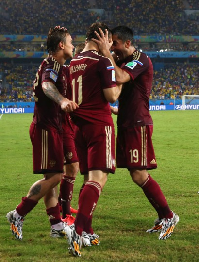 Aleksandr Kerzhakov of Russia (Center) celebrates with teammates Andrey Yeshchenko (Left) and Alexander Samedov (Right) after scoring his team's first goal during the 2014 FIFA World Cup Brazil Group H match between Russia and South Korea at Arena Pantanal on June 17, 2014 in Cuiaba, Brazil. (Elsa/Getty Images)