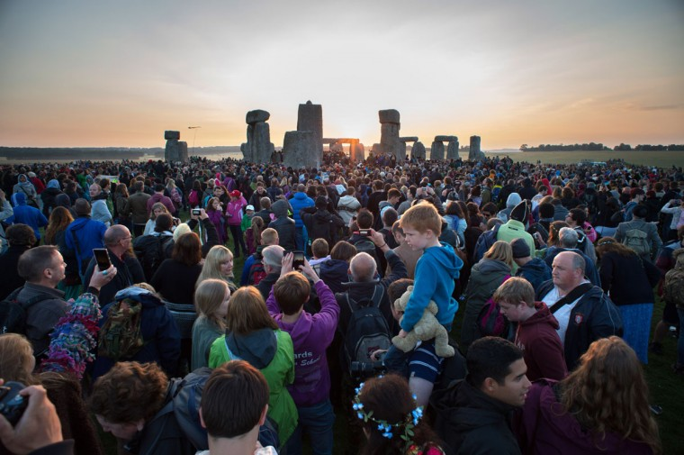 People gather to watch the Summer Solstice sunrise at Stonehenge on June 21, 2014 in Wiltshire, England. A sunny forecast brought thousands of revellers to the 5,000 year old stone circle in Wiltshire to see the sunrise on the Summer Solstice dawn. The solstice sunrise marks the longest day of the year in the Northern Hemisphere. (Photo by Tim Ireland/Getty Images)