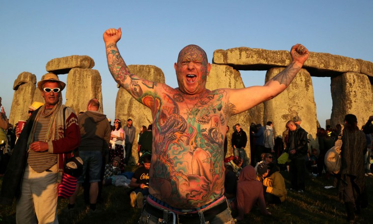 A reveler called Mad Alan celebrates the 2014 summer solstice, the longest day of the year, at sunrise at the prehistoric monument Stonehenge, near Amesbury in Southern England, on June 21, 2014. The festival, which dates back thousands of years, celebrates the longest day of the year when the sun is at its maximum elevation. Modern druids and people gather at the landmark Stonehenge every year to see the sun rise on the first morning of summer. (Geoff Caddick/AFP/Getty Images