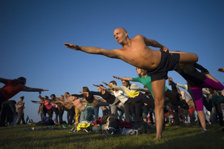 Revellers perform yoga as they celebrate the summer solstice on Salisbury Plain, in southern England June 21, 2014. Stonehenge is a celebrated venue of festivities during the summer solstice - the longest day of the year in the northern hemisphere - and it attracts thousands of revellers, spiritualists and tourists. Druids, a pagan religious order dating back to Celtic Britain, believe Stonehenge was a centre of spiritualism more than 2,000 years ago.(Kieran Doherty/Reuters)