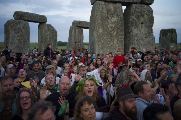 Revellers take part in incantations during a sunset ceremony as they prepare to celebrate tomorrow's summer solstice at the Stonehenge monument on Salisbury Plain in southern England June 20, 2014. Druids and revellers make the annual pilgrimage to the site to celebrate the longest day of the year. (Kieran Doherty/Reuters)