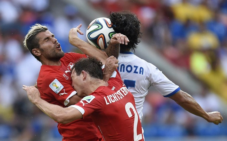 Honduras' midfielder Roger Espinoza (back) jumps to head the ball with Switzerland's midfielder Valon Behrami (Left) and defender Stephan Lichtsteiner during the Group E football match between Honduras and Switzerland at the Amazonia Arena in Manaus during the 2014 FIFA World Cup on June 25, 2014. ( Juan Barreto/Getty Images)