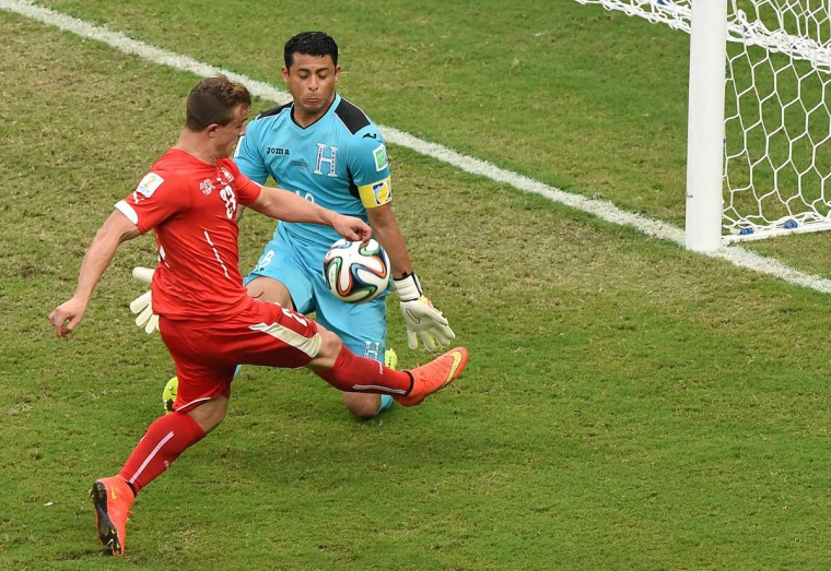 Honduras' goalkeeper Noel Valladares (back) challenges Switzerland's midfielder Xherdan Shaqiri as he advances with the ball during the Group E football match between Honduras and Switzerland at the Amazonia Arena in Manaus during the 2014 FIFA World Cup on June 25, 2014. (Luis Acosta/Getty Images)