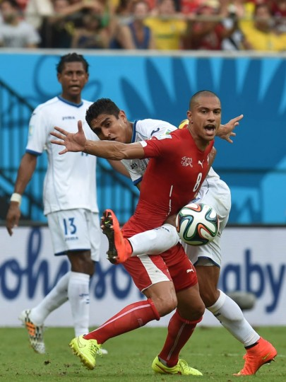 Switzerland's midfielder Goekhan Inler challenges Honduras' midfielder Jorge Claros (back) during the Group E football match between Honduras and Switzerland at the Amazonia Arena in Manaus during the 2014 FIFA World Cup on June 25, 2014. (Rodrigo Arangua/Getty Images)