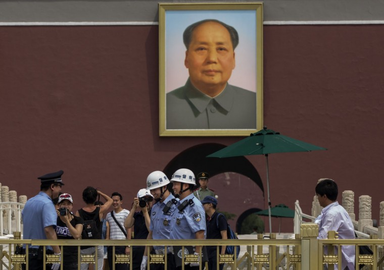 Chinese police and tourists stand underneath a picture of late leader Mao Zedong outside the Forbidden City in Tiananmen Square on June 4, 2014 in Beijing. (Photo by Kevin Frayer/Getty Images)