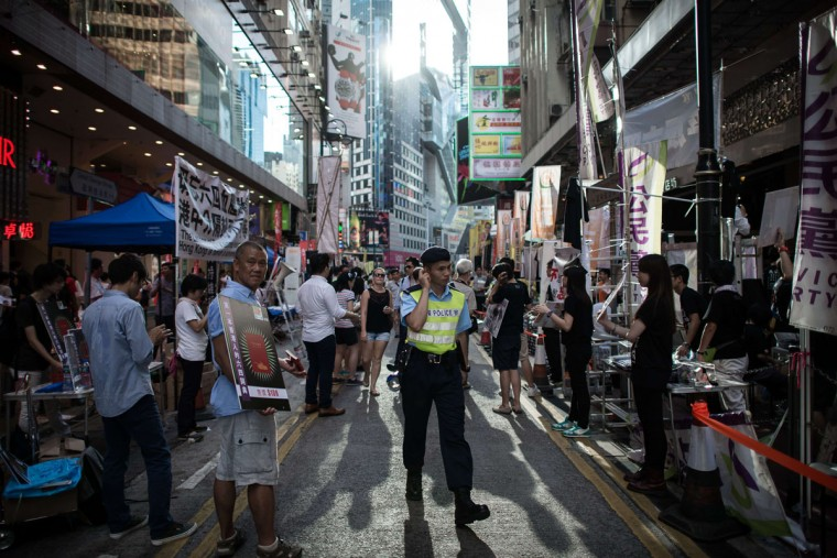 A policeman patrols a street lined by activists distributing leaflets to commemorate China's 1989 Tiananmen Square events ahead of a candlelight vigil in Hong Kong on June 4, 2014. (PHILIPPE LOPEZ/AFP/Getty Images)