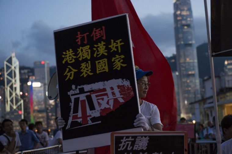 A member of a pro-China group holds a placard as she is confronted by pro-democracy activists during a rally to mark the 1989 Tiananmen Square military crackdown, in Hong Kong on June 4, 2014. (Alex Ogle/AFP/Getty Images)
