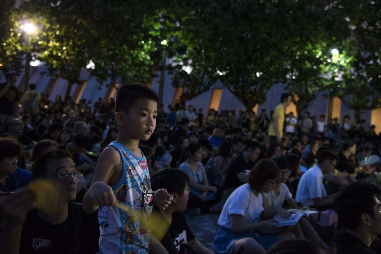 A boy waves a fan during a rally to mark the 1989 Tiananmen Square military crackdown, in Hong Kong on June 4, 2014. (Alex Ogle/AFP/Getty Images)