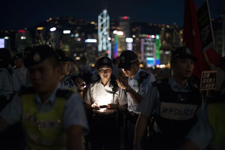 Hong Kong police officers discuss their crowd control tactics as pro-democracy activists confront a pro-China group during a rally to mark the 1989 Tiananmen Square military crackdown, in Hong Kong on June 4, 2014. (Alex Ogle/AFP/Getty Images)
