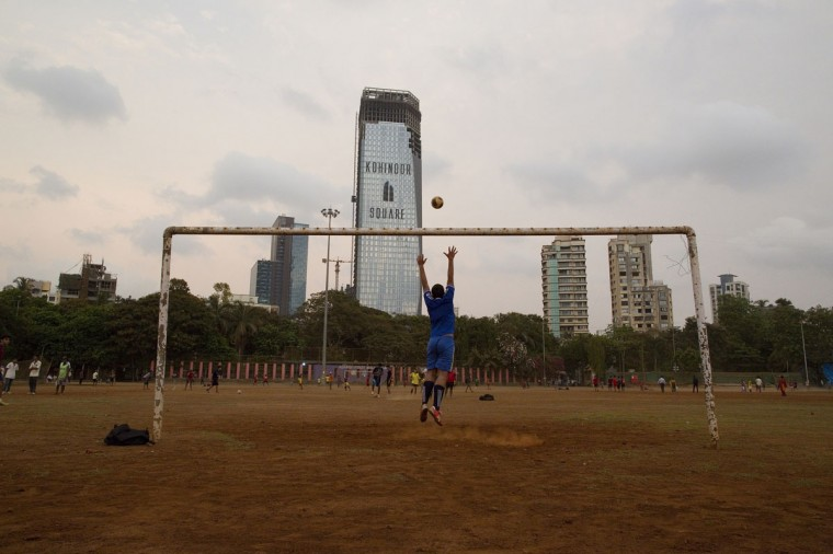 A boy jumps to save a goal while playing soccer at Shivaji Park in Mumbai, India on June 3, 2014. (REUTERS/Danish Siddiqui)