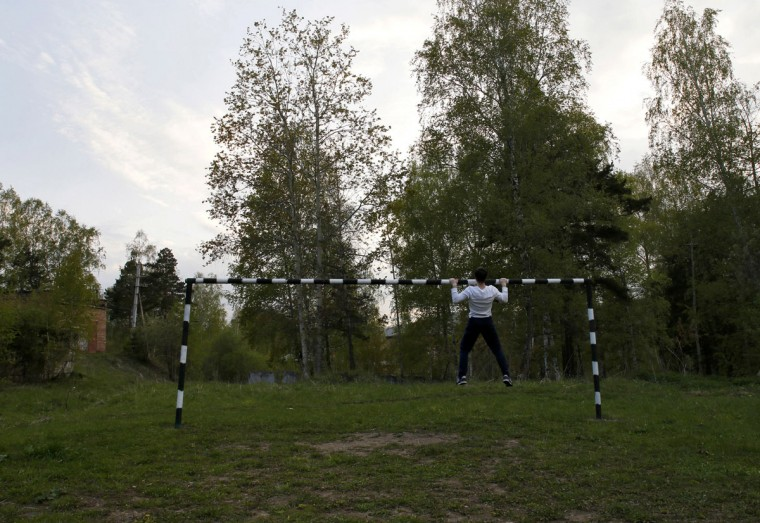 A local man trains on a goalpost at an athletic field at twilight in the town of Divnogorsk outside Russia's Siberian city of Krasnoyarsk on June 2, 2014. (REUTERS/Ilya Naymushin)