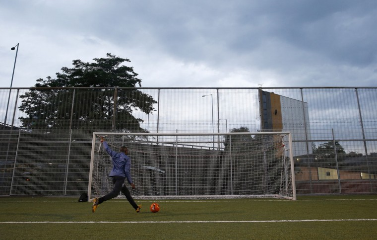 A night football league player kicks a ball into a goal at the Westway Sports Center in London on June 3, 2014. (REUTERS/Suzanne Plunkett)