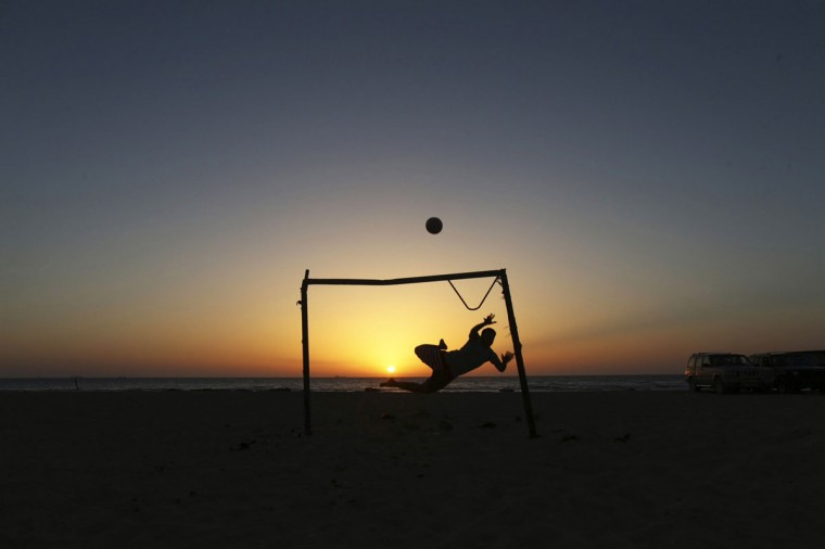 A boy jumps to save a goal while playing soccer on the beach in Benghazi, Libya on June 1, 2014. (REUTERS/Esam Omran Al-Fetori)