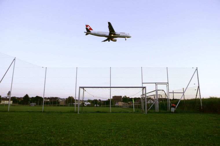 A Swiss airline jet flies over a goalpost on a soccer pitch as it approaches to land at Zurich Airport in the town of Kloten, Switzerland on May 31, 2014. (REUTERS/Arnd Wiegmann)