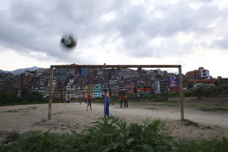 Children play soccer on a playing field in Kirtipur, Kathmandu, Nepal on May 31, 2014. (REUTERS/Navesh Chitrakar)