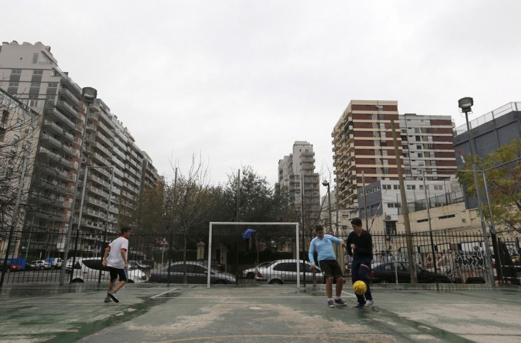 Children play in front of a soccer goalpost on a sports court in the Villa Urquiza neighborhood of Buenos Aires, Argentina on May 30, 2014. (REUTERS/Enrique Marcarian)