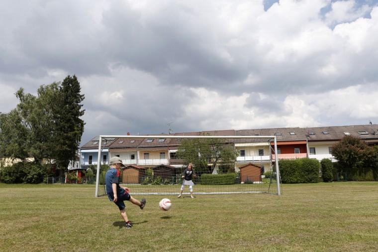 Children play near a soccer goalpost in a field in Olching near Munich, southern Germany on June 3, 2014. (REUTERS/Michaela Rehle)