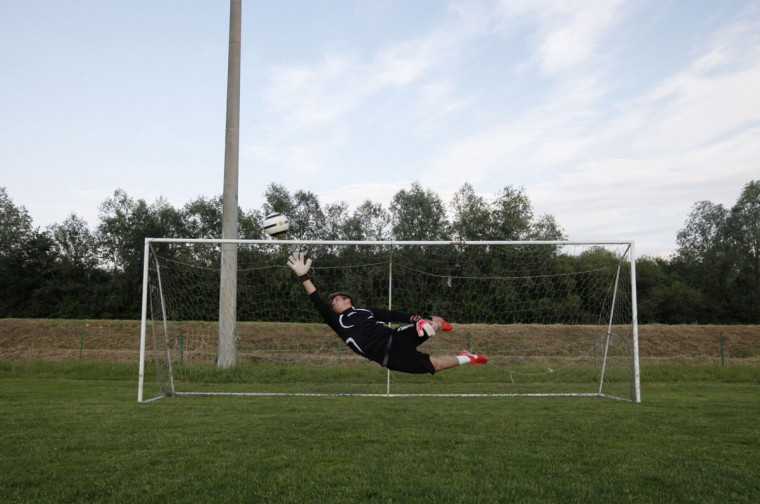 A goalkeeper jumps to save a goal during soccer practice in Vipolze, Slovenia on June 3, 2014. (REUTERS/Srdjan Zivulovic)