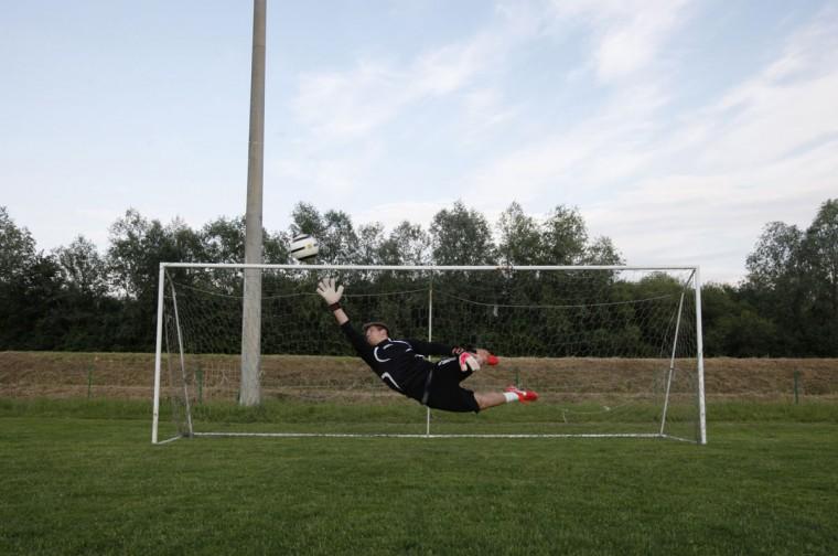A goalkeeper jumps to save a goal during soccer practice in Vipolze, Slovenia on June 3, 2014. (REUTERS/Srdjan Zivulovic)