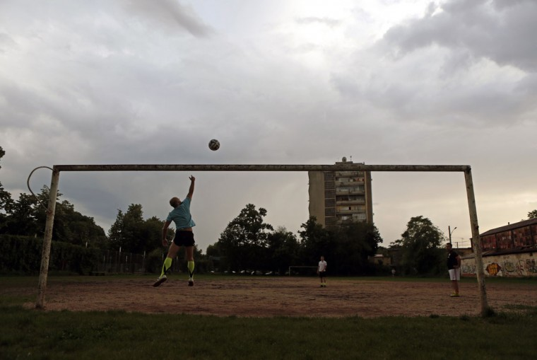 A man jumps to save a goal at dusk on a field in Bucharest, Romania on June 1, 2014. (REUTERS/Bogdan Cristel)