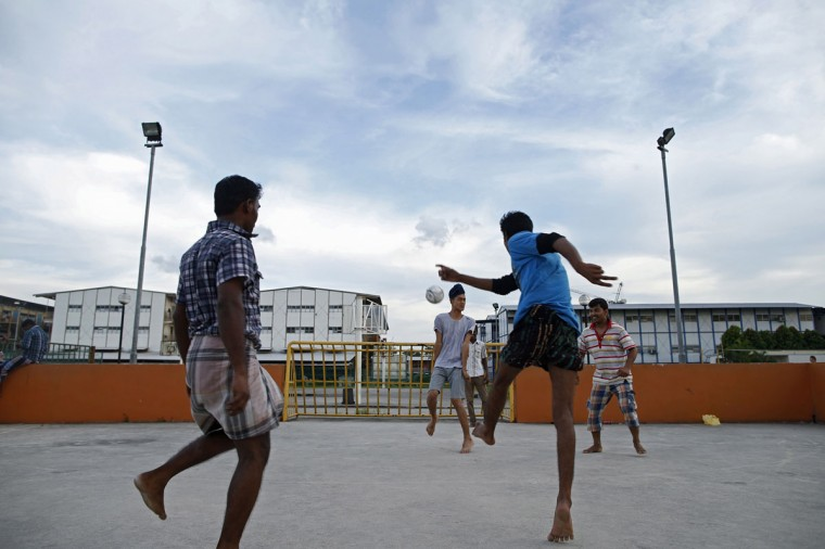 A man plays soccer with migrant workers from Bangladesh and India at a street soccer court near a workers' dormitory (behind) in Singapore on June 3, 2014. (REUTERS/Edgar Su)
