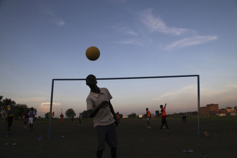 A boy plays with a ball in front of a soccer goalpost in Juba, Sudan on June 2, 2014. (REUTERS/Andreea Campeanu)