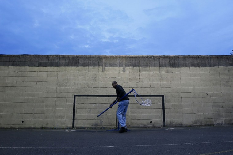 A man removes a netball goal from in front of a painted soccer goalpost at Chestnut Grove School in Balham, south London on June 3, 2014. (REUTERS/Stefan Wermuth)