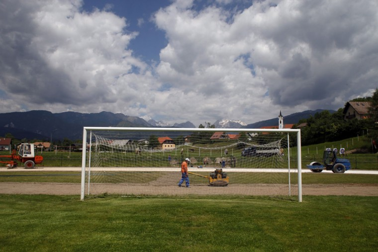 A worker walks past a soccer goalpost at a playing field in Kamnik, Slovenia on June 2, 2014. (REUTERS/Srdjan Zivulovic)