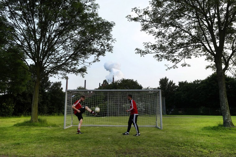 Two men kick a ball on a soccer field in front of a coking plant in the western city of Bottrop, Germany on June 2, 2014. (REUTERS/Ina Fassbender)