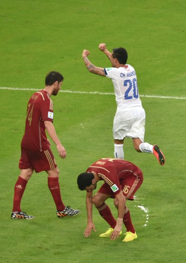 Chile's midfielder Charles Aranguiz (R) celebrates after scoring a goal as Spain's midfielder Xabi Alonso (L) and Spain's midfielder Sergio Busquets react during a Group B football match between Spain and Chile in the Maracana Stadium in Rio de Janeiro during the 2014 FIFA World Cup on June 18, 2014. (Yasuyoshi Chiba/AFP/Getty Images)