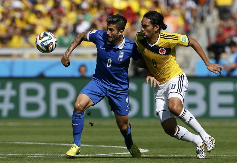 Greece's Panagiotis Kone (L) fights for the ball with Colombia's Abel Aguilar during their 2014 World Cup Group C soccer match at the Mineirao stadium in Belo Horizonte June 14, 2014. (Sergio Perez/Reuters)