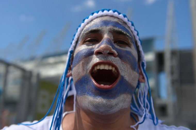 An Uruguayan supporter poses in front of Castelao Stadium in Fortaleza ahead of the Group D football match between Uruguay and Costa Rica during the 2014 FIFA World Cup on June 14, 2014. (Gabriel Bouys/AFP/Getty Images)