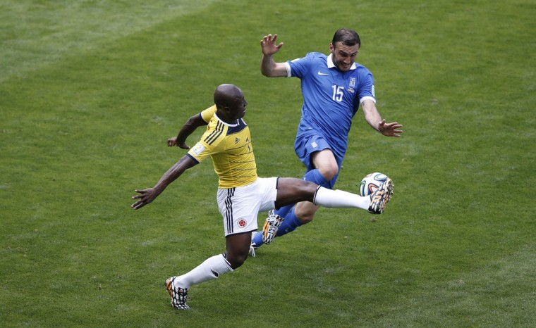 Greece's defender Vasilis Torosidis (R) vies with Colombia's defender Pablo Armero (L) during a Group C football match between Colombia and Greece at the Mineirao Arena in Belo Horizonte during the 2014 FIFA World Cup on June 14, 2014. (Adrian Dennis/AFP/Getty Images)