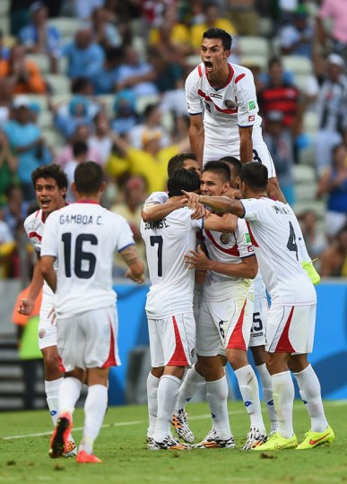 Giancarlo Gonzalez of Costa Rica jumps on his teammates as they celebrate the team's second goal by Oscar Duarte (C) during the 2014 FIFA World Cup Brazil Group D match between Uruguay and Costa Rica at Castelao on June 14, 2014 in Fortaleza, Brazil. (Photo by Laurence Griffiths/Getty Images)
