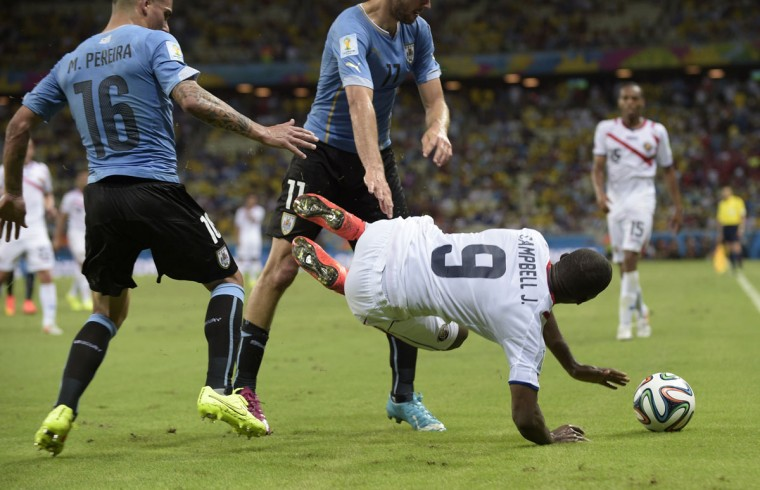 Uruguay's defender Maximiliano Pereira (L) tackles Costa Rica's forward Joel Campbell (R) during a Group D football match between Uruguay and Costa Rica at the Castelao Stadium in Fortaleza during the 2014 FIFA World Cup on June 14, 2014. (Daniel Garcia/AFP/Getty Images)