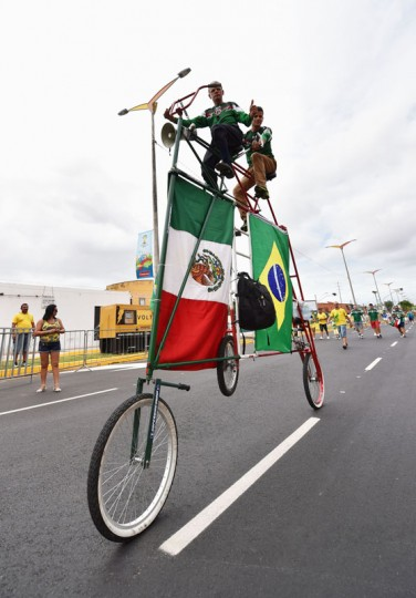Fans ride a bicycle outside the stadium prior to the 2014 FIFA World Cup Brazil Group A match between Brazil and Mexico at Castelao on June 17, 2014 in Fortaleza, Brazil. (Photo by Buda Mendes/Getty Images)